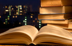 Books. On a table, a back background - a night city stock photos