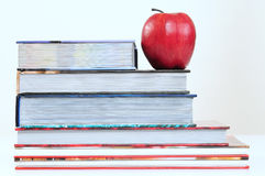 Books. Overlapped series of thick books with red apple Royalty Free Stock Photos