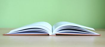 Books. One open book with green background stock photos