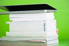 Books. Laptop and collection of books isolated over a green background Stock Photos
