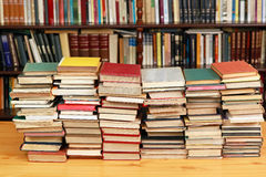 Books. Large pile of old books with library shelves in the background Royalty Free Stock Images