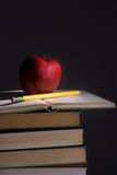 Books. A pile of books with an apple and pencil cast shadows across the room Royalty Free Stock Photos