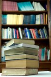 Books. A pile of books, against the background of even more books on the shelves Stock Photo