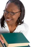 By books - adult education. African-American Female Student by stack of books Royalty Free Stock Image