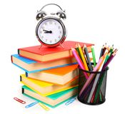 Books, an alarm clock and school tools. Stock Photo