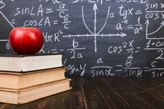 Free Books And An Apple On A Wooden Table, Against The Background Of A Chalkboard With Formulas. Teacher&x27;s Day Concept And Back To Royalty Free Stock Photo - 153380105