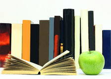 Books and apple. A open book and a green apple in front of a row of books isolated on a white background royalty free stock image