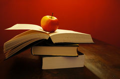 Books and a apple. Some books with an apple on the top in a dark room Royalty Free Stock Images