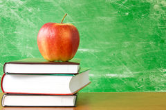 Books with apple against dirty chalkboard Royalty Free Stock Image