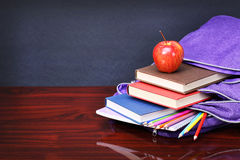 Books, apple, backpack and pencils on wood desk table Royalty Free Stock Photography