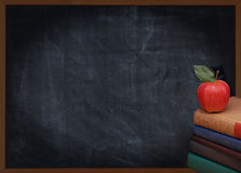 Books Apple and Chalkboard. A stack of books with a red apple on top in front of an out of focus chalkboard. Back to school or education concept. Vintage effect Royalty Free Stock Photography