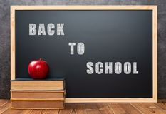Books and apple in front of black board written with BACK TO SCHOOL, THE  WORDS WITH CLIPPING PATH AND CAN BE DELETED DIRECTLY. Books and apple in front of a royalty free stock images