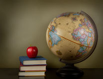 Books with an apple next to a globe Royalty Free Stock Image