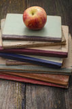 Books and Apple. Apple and old school books stacked on a wooden table Stock Image