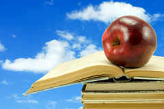 Books with apple on sky background Royalty Free Stock Photos