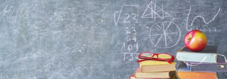 Books, apple, specs in front of a black board,back to school royalty free stock photography