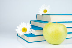 Books, apple and white flower. Group of blue book, yellow apple and white flowers Stock Photo