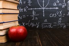 Books and an apple on a wooden table, against the background of a chalkboard with formulas. Teacher& x27;s day concept and back to. Books and an apple on wooden royalty free stock image