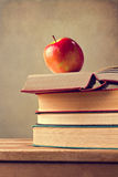Books and apple on wooden table Stock Image