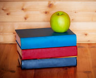 Books and apple on wooden table over wooden background Royalty Free Stock Photos