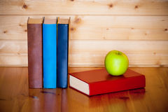 Books and apple on wooden table over wooden background Royalty Free Stock Image