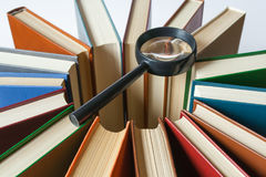 Books are arranged in a circle in the center on them lies a magnifying glass (search concept). Colorful books are arranged in a circle in the center on them lies stock photos