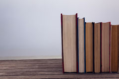 Books arranged on wooden table. Against white background royalty free stock photos