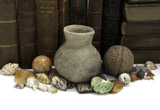 Books and Artifacts. A row of books with a grouping of ancient and natural artifacts Stock Photo
