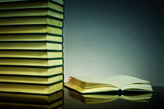 Books background. A stack of books and an open book with blank sheets on a dark background (for any design ideas stock photo