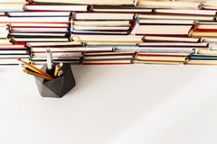 Books background, glasses, pens and pencils on white wooden table.  royalty free stock image