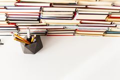 Books background, glasses, pens and pencils on white wooden table.  stock photo