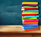 Row of of colorful books on blackboard background. Books background paper art abstract brown dark Stock Photos