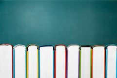 Row of of colorful books on blackboard backgtound. Books background paper art abstract brown dark Royalty Free Stock Photos