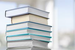 Stack of colorful books on bkurred background. Books background paper art abstract brown dark Stock Photos