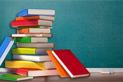 Stack of colorful books on wooden table. Books background paper art abstract brown dark Stock Photography