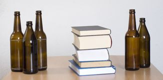Books and beer bottles. On the table Royalty Free Stock Photography