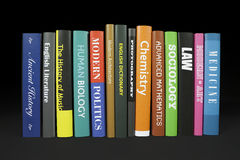 Books on black. A row of books with mocked up covers of various subjects Royalty Free Stock Images
