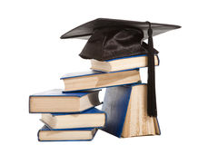 Books with black cap of bachelor isolated on white Royalty Free Stock Photos