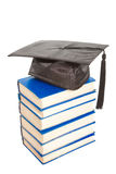 Books with black cap of bachelor isolated on white Stock Photography