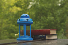 Books and blue lamp. Garden wooden table with books and blue lamp Stock Photos