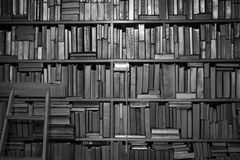 Books on bookcase in black and white. Unmarked bound books on shelves on wall inside with wooden ladder in black and white stock photo