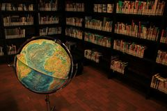 Books in different colours in the library. The books  in bookcases for rent and a globe in the municipal library, Boekenberg in the city Spijkenisse Royalty Free Stock Images