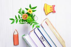 Books, bookmark glasses, gingerbread pencil and yellow bell, chrysanthemum on a white wooden background royalty free stock images