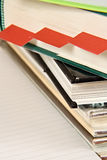 Books and Bookmarks. A pile of books next to a sheet of paper, with three red bookmarks inserted in one of the books Stock Image