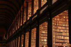 Books, books and more books. The library of the trinity college is an amazing place for a book lovers. Additionally it provides awesome light to visualize them Royalty Free Stock Photos