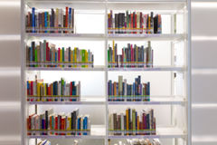 Books on bookshelf in library room, abstract blur de focused bac Royalty Free Stock Photos