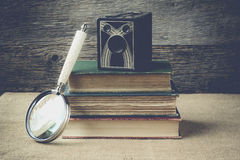 Books, camera, and magnifying glass on retro background with Ins Stock Images
