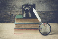 Books, camera, and magnifying glass on retro background with Ins Royalty Free Stock Photos
