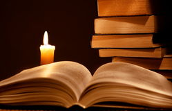 Books and candle. On a table, a back background - black royalty free stock photography