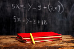 Books and chalk by blackboard with equation. Two red books on school desk with blackboard in the background royalty free stock photography